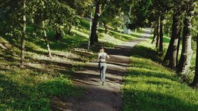 Young attractive girl running in city park. Woman running in wood aerial back view. 4K, tracking shot. Young attractive girl running in city park. Woman running stock video