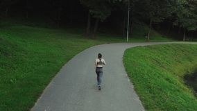 Young attractive girl running in city park. Woman running in wood aerial back view. 4K, tracking shot. Young attractive girl running in city park. Woman running stock video footage