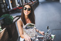 Young attractive girl on scooter Royalty Free Stock Photos