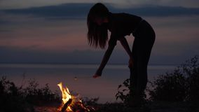 Young attractive girl on seaside with bonfire making marshmallows with a fire in cozy summer evening. Young attractive girl on seaside with bonfire making stock footage