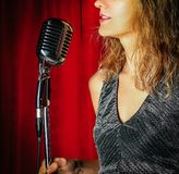 Young attractive girl singing on stage with microphone against t. He background of red curtains royalty free stock photo