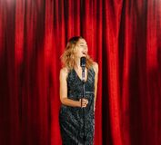 Young attractive girl singing on stage with microphone against t. He background of red curtains stock photo