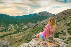 Young attractive girl sits on the edge of the cliff stock photos