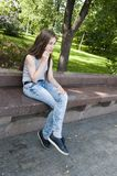 Young attractive girl sitting on bench. Summer park. Smile. Photo Royalty Free Stock Image