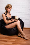 Young attractive girl sitting on a chair with a cap of tea Royalty Free Stock Photography