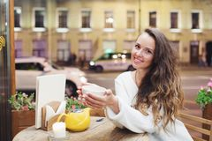 Young attractive girl sitting in the evening in a cafe stock photography