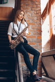 Young attractive girl sitting on handrail in white shirt with a saxophone - outdoor. young woman with sax looking at camera stock photo