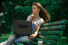 A young attractive girl sitting in a park with a laptop Stock Photos