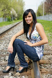Young attractive girl sitting on a railroad Royalty Free Stock Photos