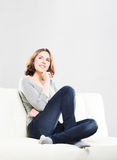 Young and attractive girl sitting on a sofa at home Stock Images