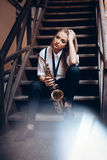 Young attractive girl sitting on steps in white shirt with a saxophone - outdoor in old town. young woman with sax thinking a Stock Images
