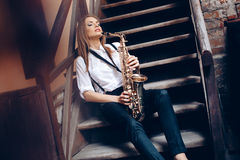 Young attractive girl sitting on steps in white shirt with a saxophone - outdoor in old town. young woman with sax thinking a Stock Photo