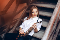 Young attractive girl sitting on steps in white shirt with a saxophone - outdoor in old town. young woman with sax thinking a Royalty Free Stock Image