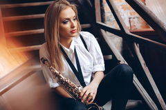 Young attractive girl sitting on steps in white shirt with a saxophone - outdoor in old town. young woman with sax thinking a Royalty Free Stock Images