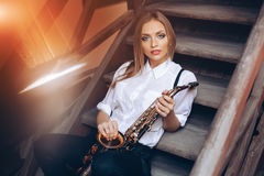 Young attractive girl sitting on steps in white shirt with a saxophone - outdoor. young woman with sax looking at camera Royalty Free Stock Images