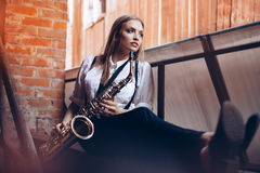 Young attractive girl sitting in white shirt with a saxophone - outdoor in old town. young woman with sax watching at camera Stock Photos