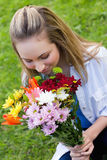 Young attractive girl smelling a bunch of flower Stock Image
