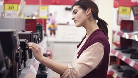 Young attractive girl smiling and dancing while looking for audio system and choosing speaker from a row of variety in. An electronics store. Bying household stock footage