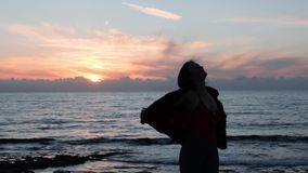 Young attractive girl spinning around and smiling at camera. Silhouette of girl dancing on seashore at dusk. Hot caucasian woman d stock video footage