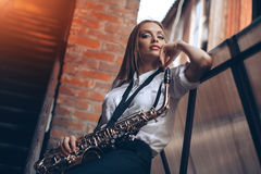 Young attractive girl standing in white shirt with a saxophone - outdoor in old town. young woman with sax looking at camera Royalty Free Stock Photography