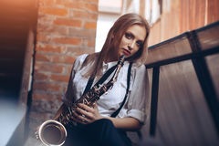 Young attractive girl standing in white shirt with a saxophone - outdoor in old town. young woman with sax looking at camera Royalty Free Stock Images