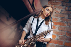 Young attractive girl standing in white shirt with a saxophone - outdoor in old town. young woman with sax thinking about som royalty free stock photography