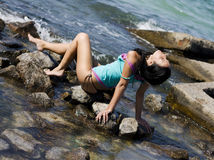 Young attractive girl on the stones. Young attractive girl is staying on the stones in the sea Stock Photos