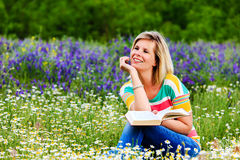 Young attractive girl studying in a flowery meadow. Royalty Free Stock Photo