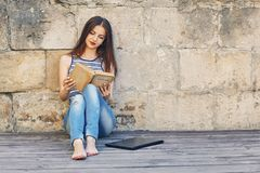 Girl studying and reading a book. Relax, rest, education concept, recreation . Young attractive girl studying and reading a book on a wooden floor . Relax, rest Royalty Free Stock Photography