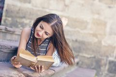 Young attractive girl studying and reading a book on a wooden floor. Relax, rest, education concept, recreation Royalty Free Stock Image