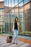 Young attractive girl with a suitcase goes on the terminal Royalty Free Stock Photo