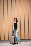 Young attractive girl with a suitcase goes on the terminal Stock Images