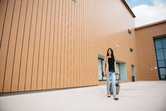 Young attractive girl with a suitcase goes on the terminal Stock Photos