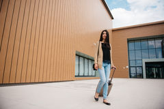 Young attractive girl with a suitcase goes on the terminal Stock Photo