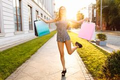 Young attractive girl in sunglasses, enjoys a successful shopping, jumping with happiness on the background of a beautiful sunset royalty free stock photography