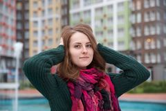 young attractive girl in a sweater and scarf, poses for a portrait on the background of urban buildings and the fountain with his royalty free stock photo