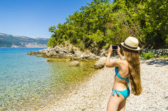Young attractive girl taking photo on beach Royalty Free Stock Photo