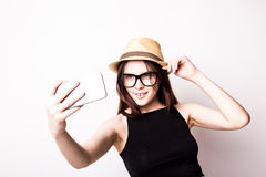 Young attractive girl taking selfie photo portrait with mobile phone or camera wearing sunglasses hat and summer dress Stock Photos