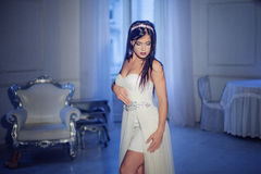 Young attractive girl in tiara and white dress. Interior on the background Royalty Free Stock Photography