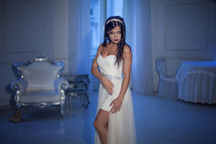 Young attractive girl in tiara and white dress. Interior on the background Royalty Free Stock Photo