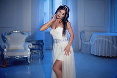 Young attractive girl in tiara and white dress. Interior on the background Royalty Free Stock Images