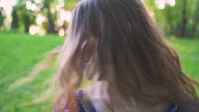 Young attractive girl twirls hair in the park closeup.