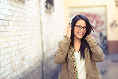 Young attractive girl in urban background. Portrait of young attractive girl in urban background hearing music with headphones Stock Images