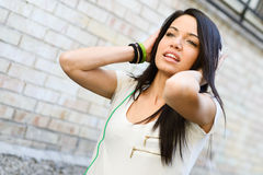 Young attractive girl in urban background. Portrait of young attractive girl in urban background hearing music with headphones Stock Photo