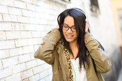 Young attractive girl in urban background. Portrait of young attractive girl in urban background hearing music with headphones Royalty Free Stock Photos