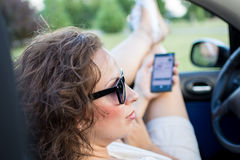 Young attractive girl using mobile phone in her car. Young attractive girl sitting in her car and holding mobile phone.She is wearing black glasses and white royalty free stock image