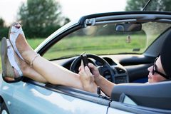 Young attractive girl using mobile phone in her car. She is wearing black glasses, white sandals with platform and white shirt. Mobile phone is black, while stock images