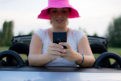 Young attractive girl using mobile phone in her car. She is wearing pink hat and white shirt. Mobile phone is black, while coupe cabriolet car is bright blue stock photo