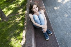 Young attractive girl waiting a call sitting on the bench. Summer park. Photo Stock Images