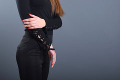 Young attractive girl wearing black trousers and black blouse. Casual style. Young attractive girl wearing black trousers and black blouse keeping both hands on royalty free stock images